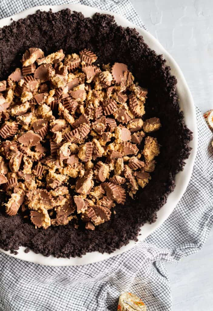 Crumbled peanut butter cups on top of Oreo crust in pie dish.