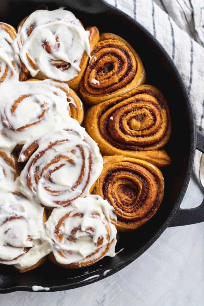 Pumpkin spice cinnamon rolls with cream cheese glaze in a cast iron pan.