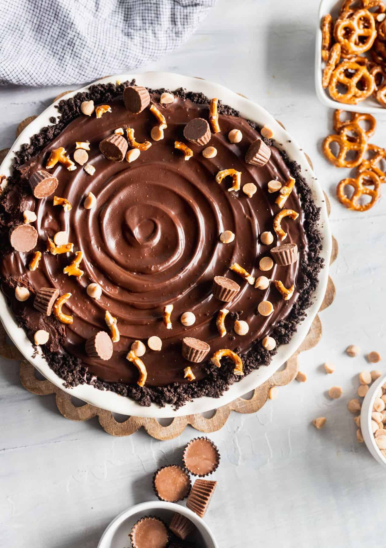 Chocolate peanut butter cup pie in a pie dish with pretzels, and peanut butter cups scattered around