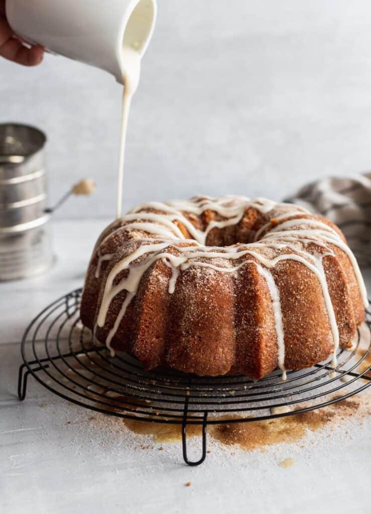 Pour apple cider glaze on top of apple cider donut cake.