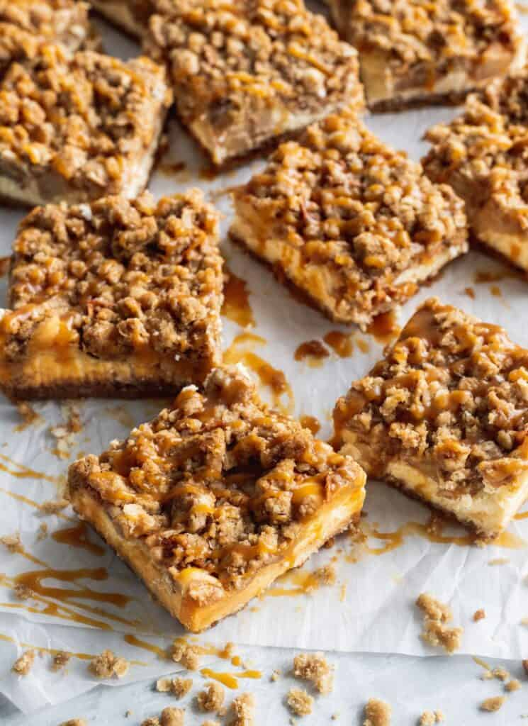 Cut up caramel apple cheesecake bars spread out on a parchment paper.