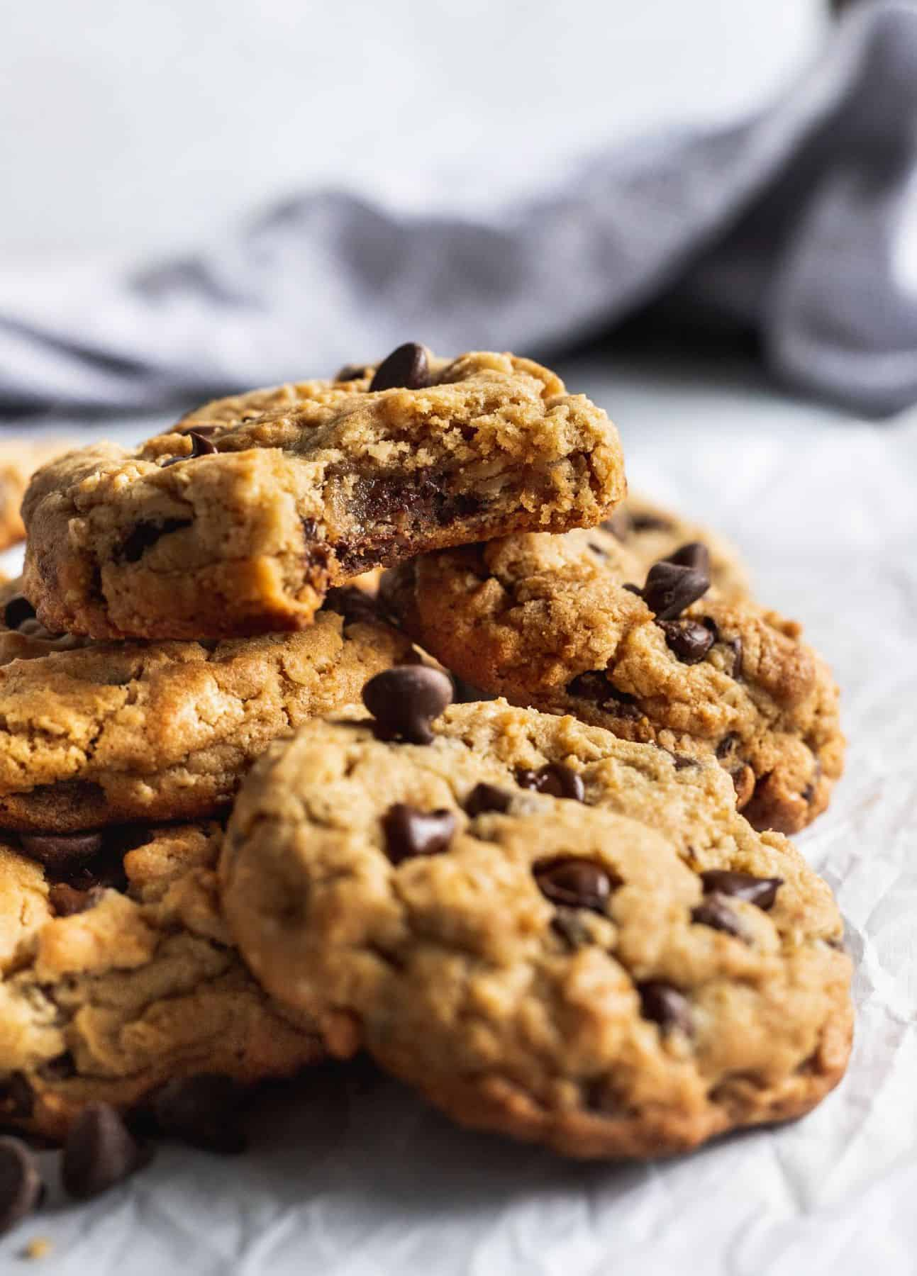 A pile of oatmeal peanut butter chocolate chip cookies with 1 cookie with a bite missing on top.