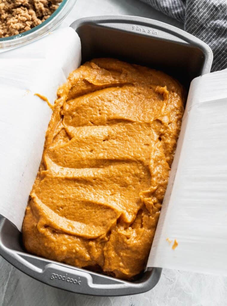 Pumpkin batter in a loaf pan with parchment paper.