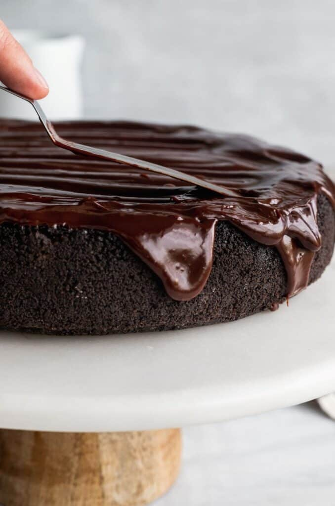 Spreading chocolate ganache on top of the cheesecake on a cake stand.