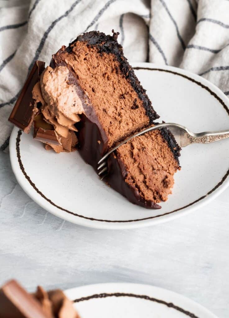 1 slice of triple chocolate cheesecake with a fork inside.