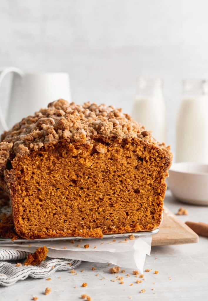 Side view of pumpkin bread with cinnamon icing on a grate.