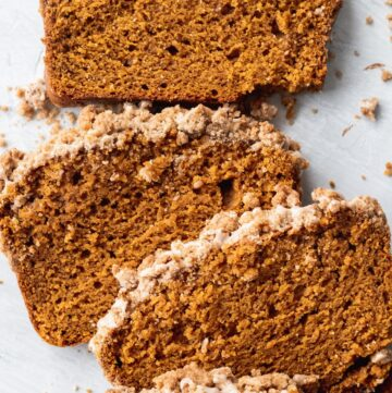 Close up of slices of pumpkin bread with cinnamon icing and pumpkin spice streusel.