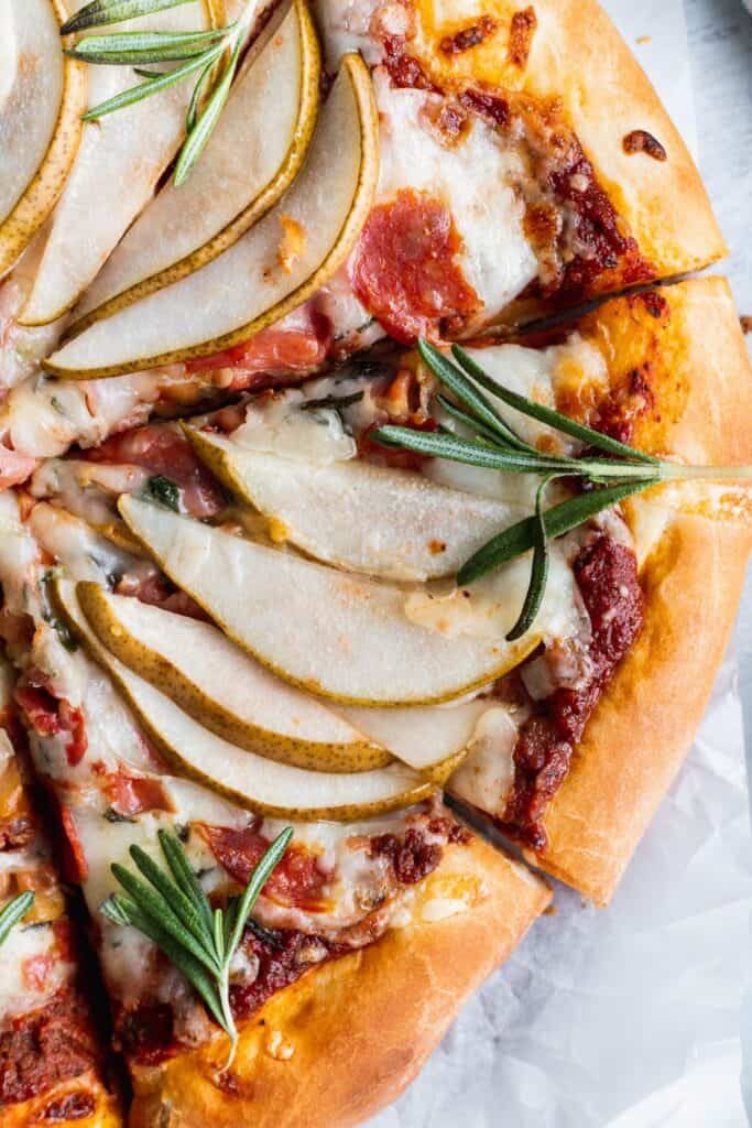 Close up of pear pizza with rosemary on top