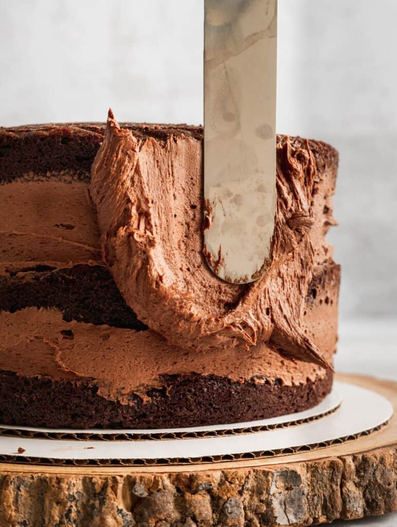 Spreading chocolate frosting on a cake.