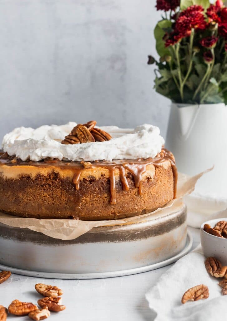 Cinnamon pecan pie cheesecake showing the pecan topping dripping down.