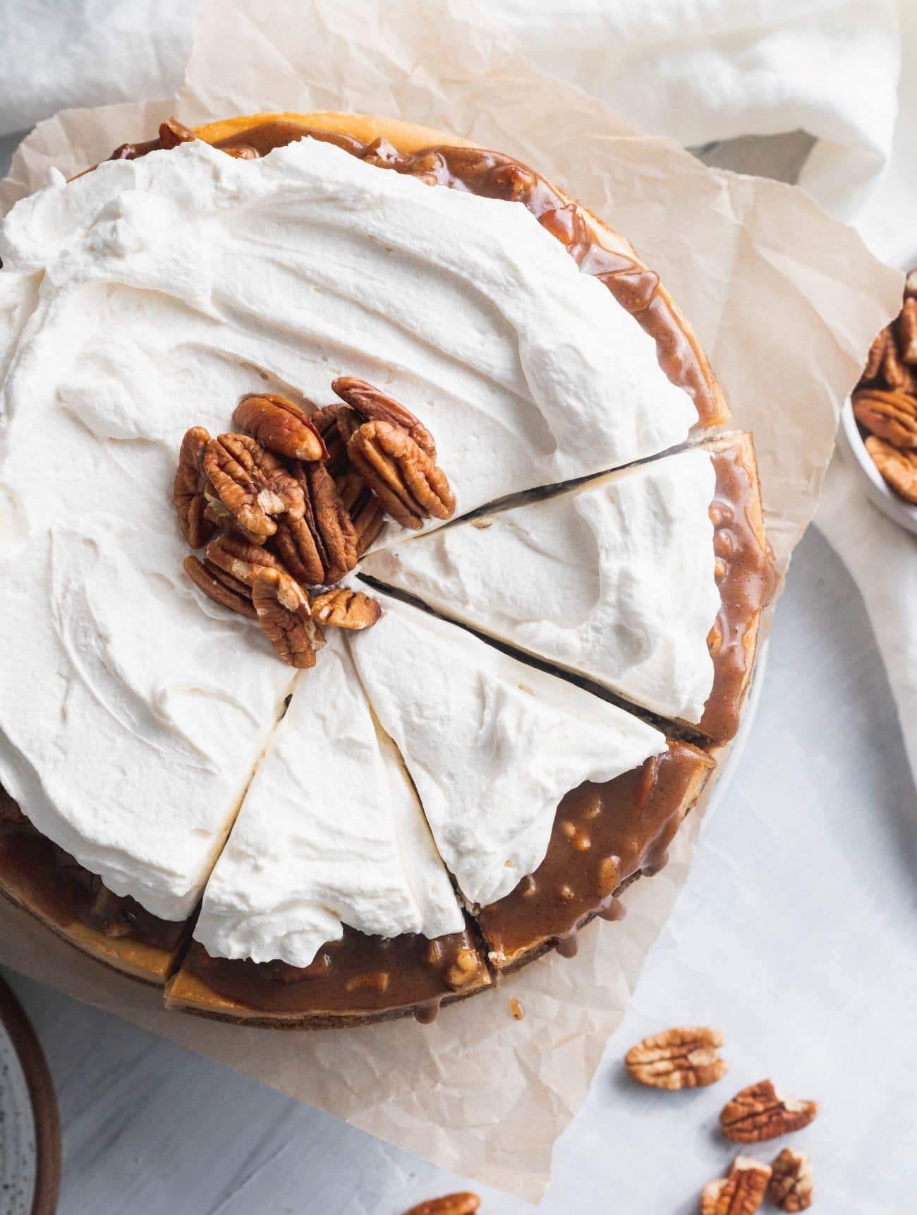 Cinnamon pecan pie cheesecake top view cut into 3 pieces.
