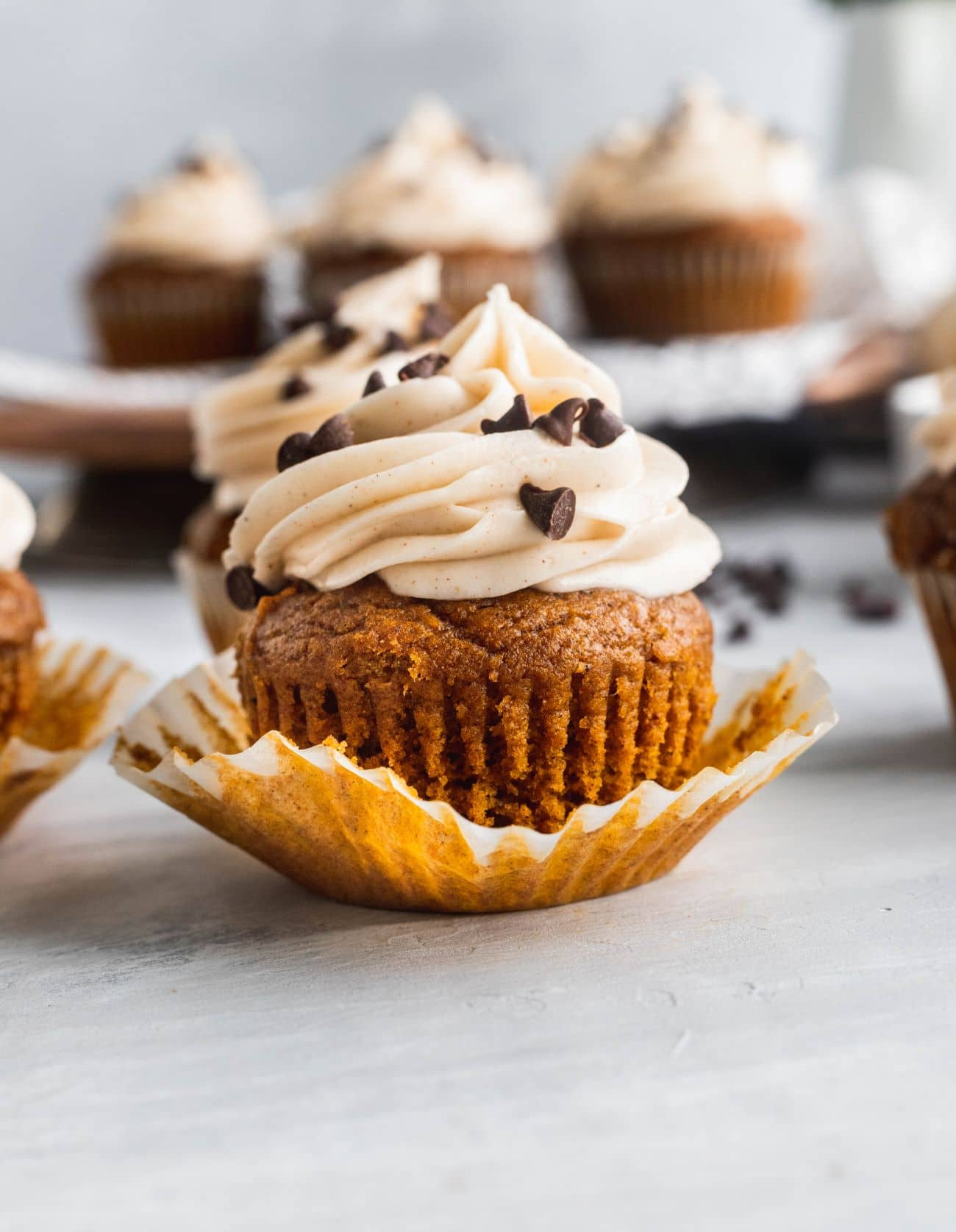 Chocolate stuffed pumpkin cupcakes with 1 unwrapped.