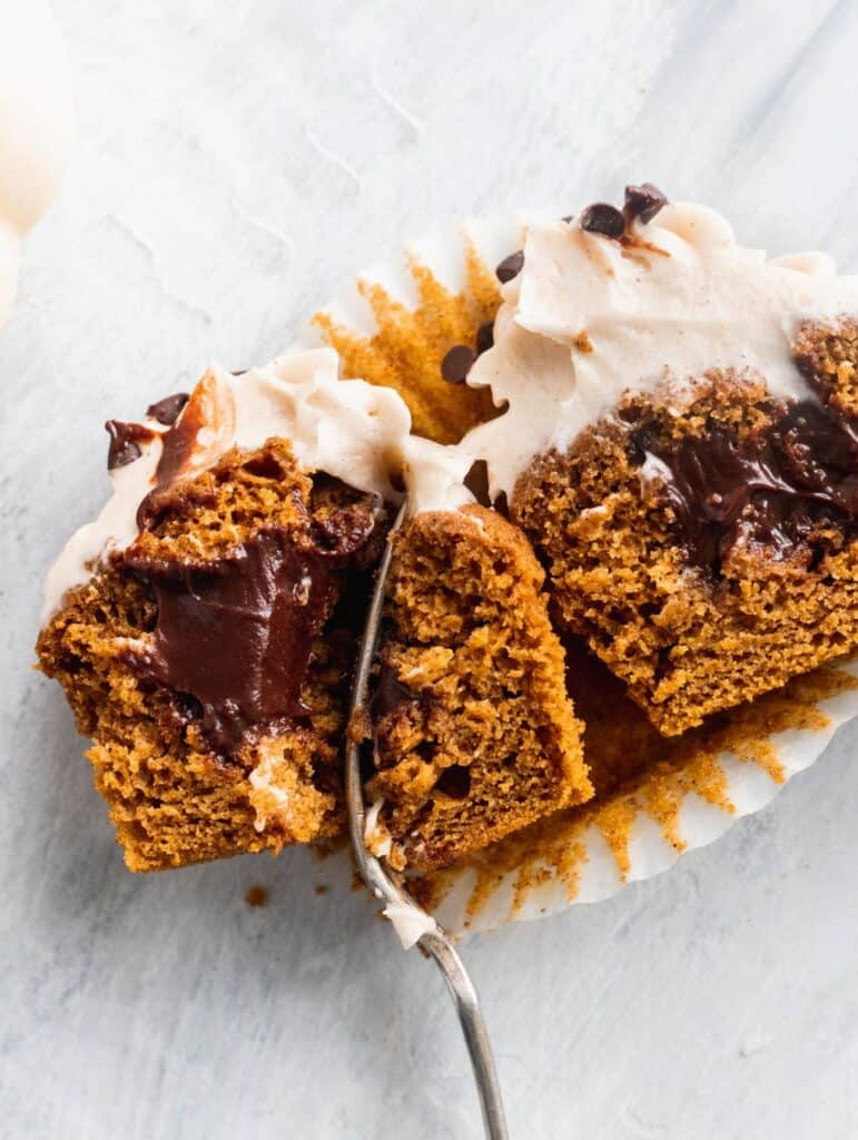 Chocolate stuffed pumpkin cupcakes split in half to see the chocolate filling.