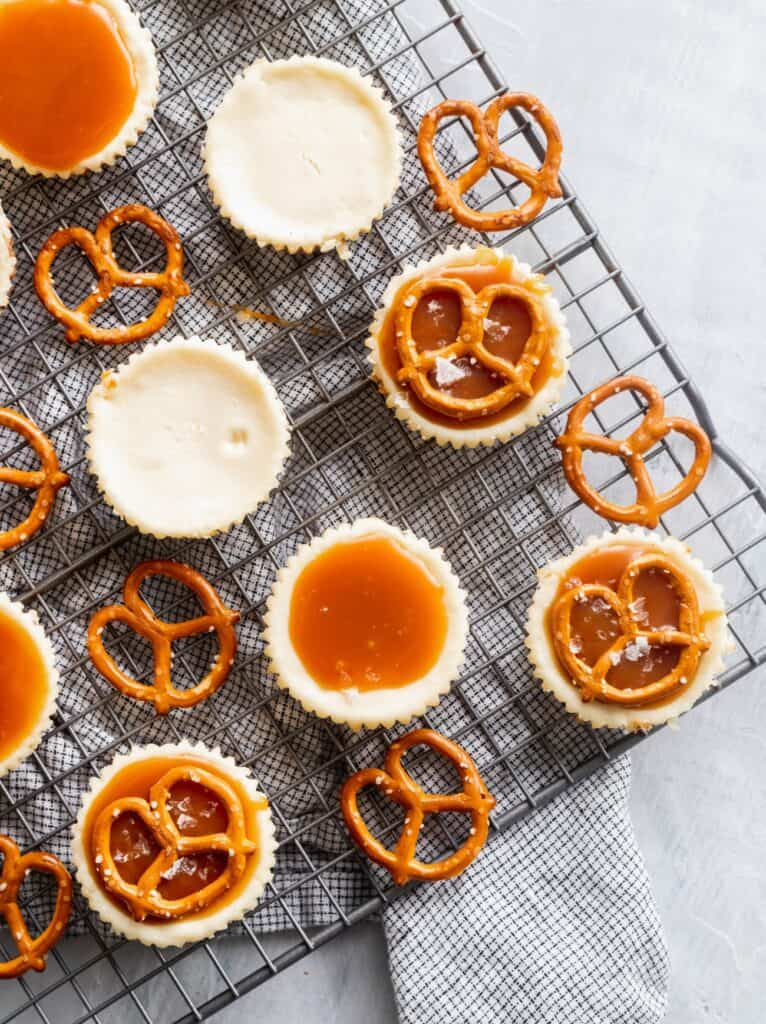 Decorating mini cheesecakes with caramel and pretzels.