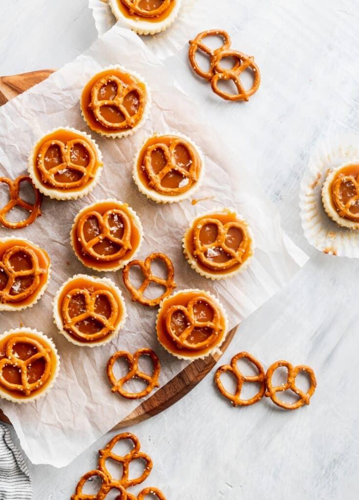 Pretzel salted caramel mini cheesecakes on a cutting board.