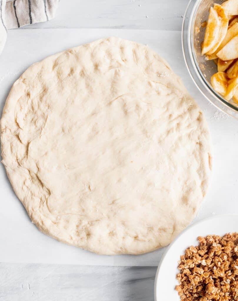 Pizza dough on a parchment paper.