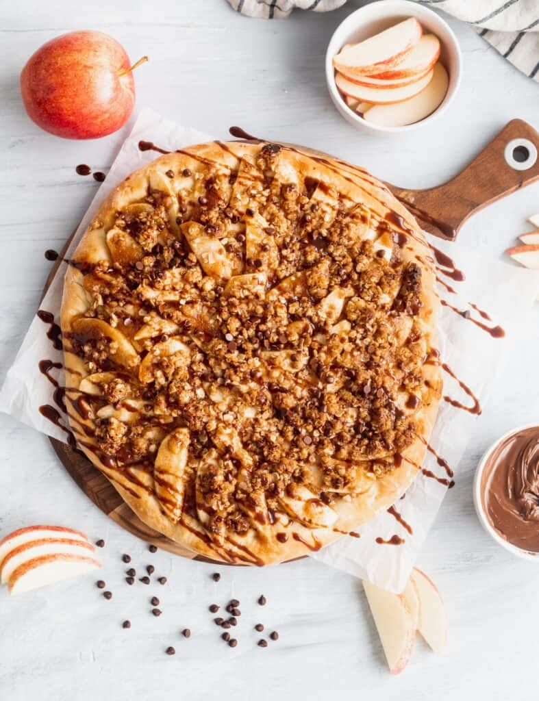 Apple Nutella dessert pizza on top of a wooden cutting board.