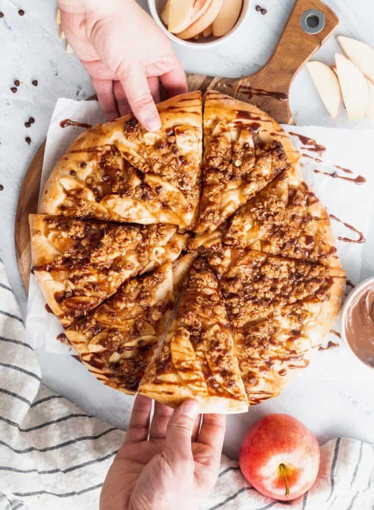 2 hands grabbing the apple Nutella dessert pizza.