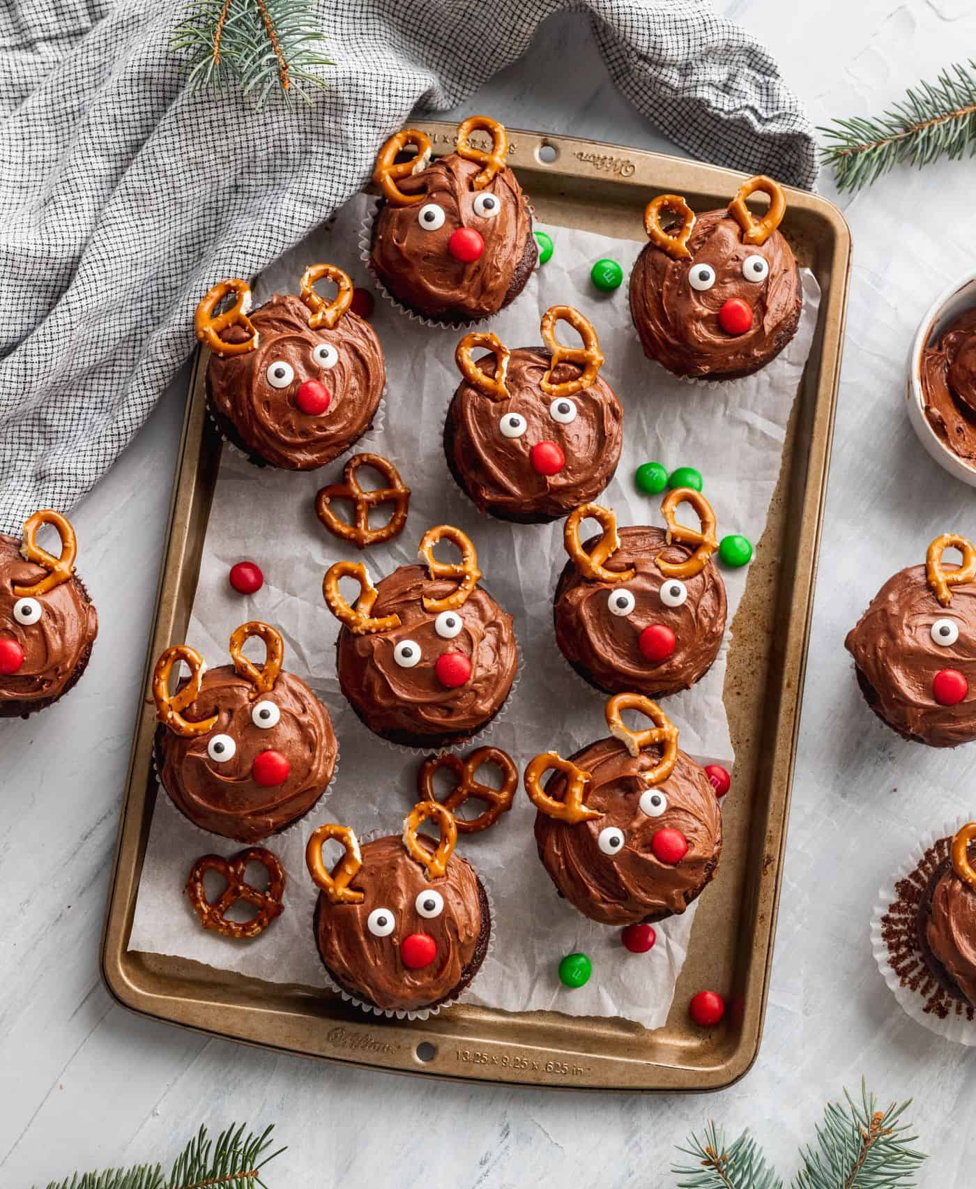 Christmas reindeer cupcakes on a cookie sheet with extra pretzels.