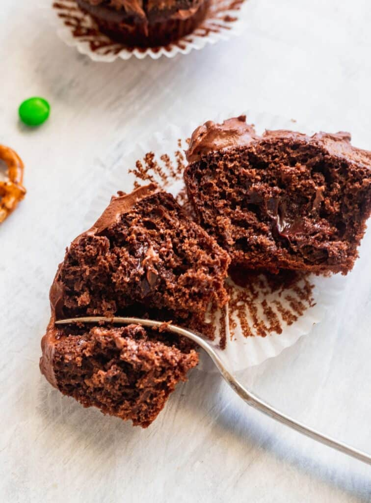 Chocolate cupcake split in half to show the filled hot fudge.