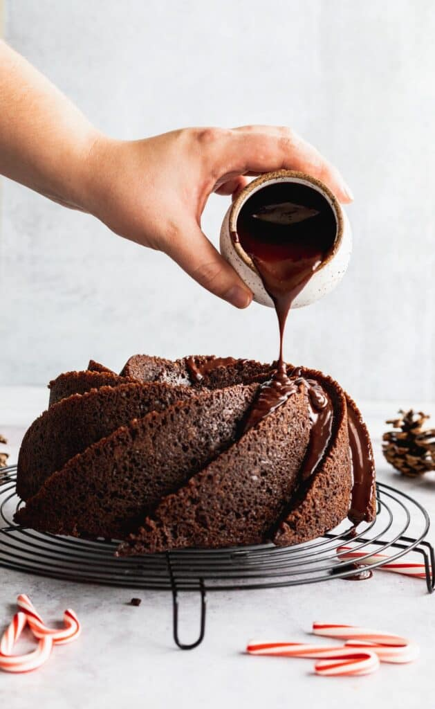 Pouring chocolate ganache over the cake.