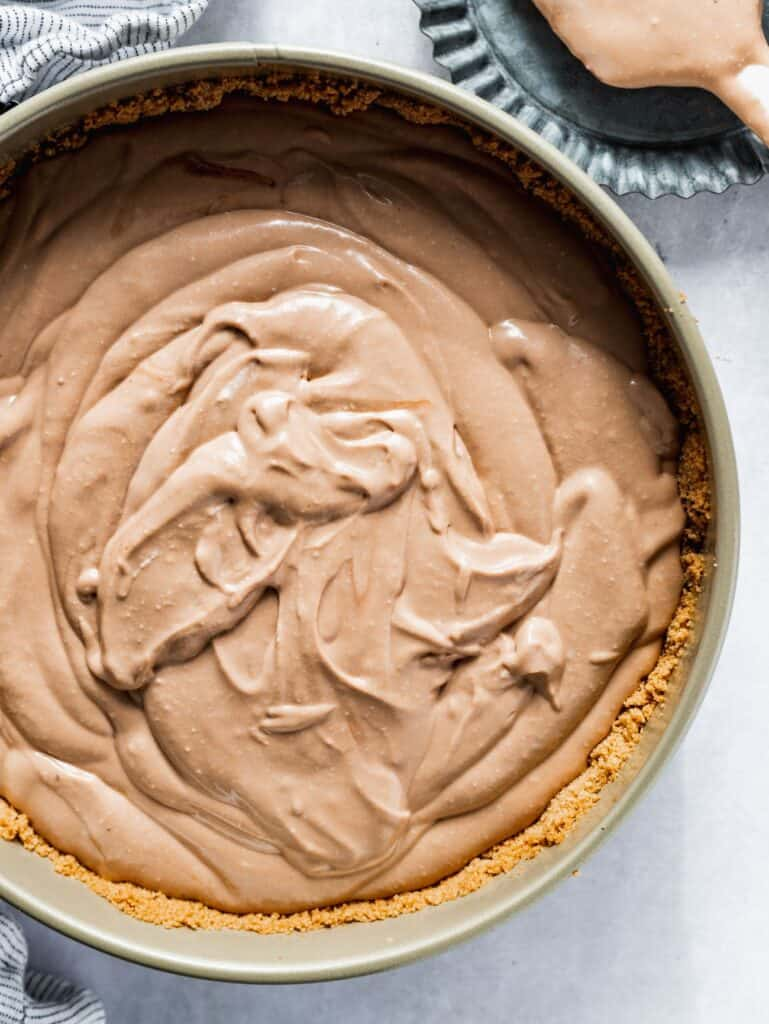 Chocolate cheesecake batter in a spring form pan.