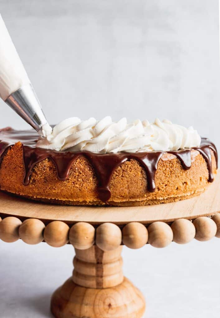 Piping on the whipped cream on top of the chocolate.