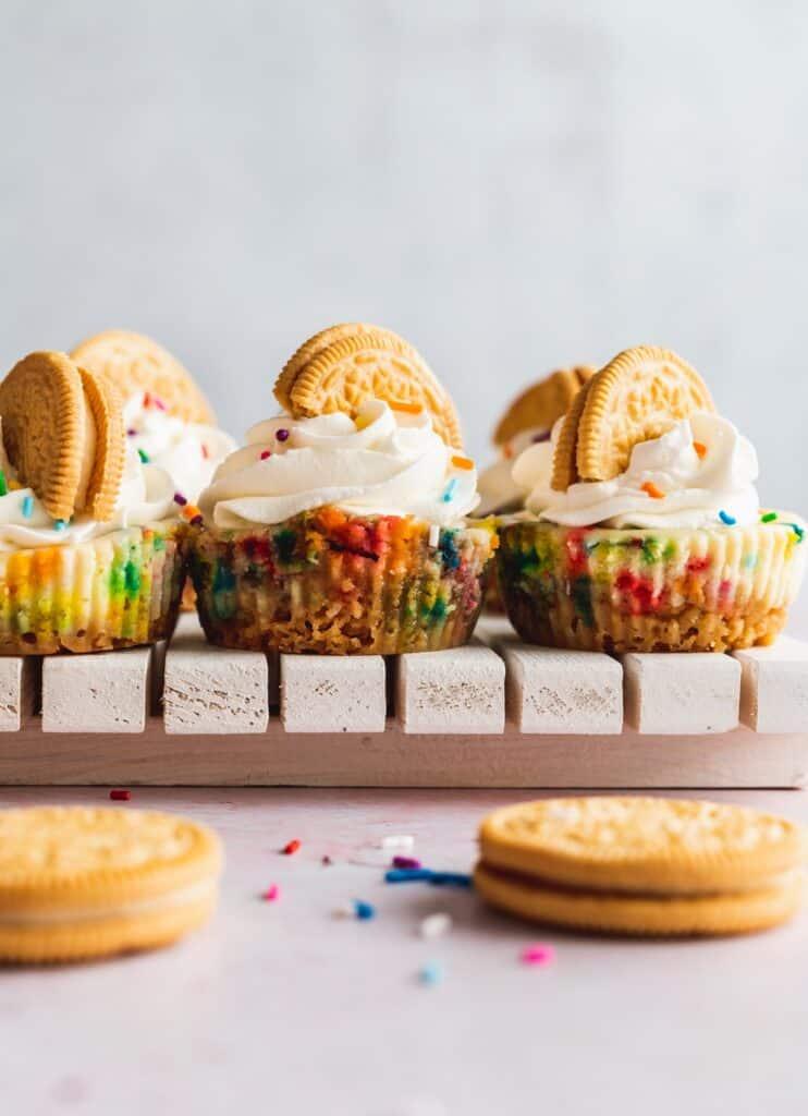Mini funfetti cheesecake with golden Oreos on top.
