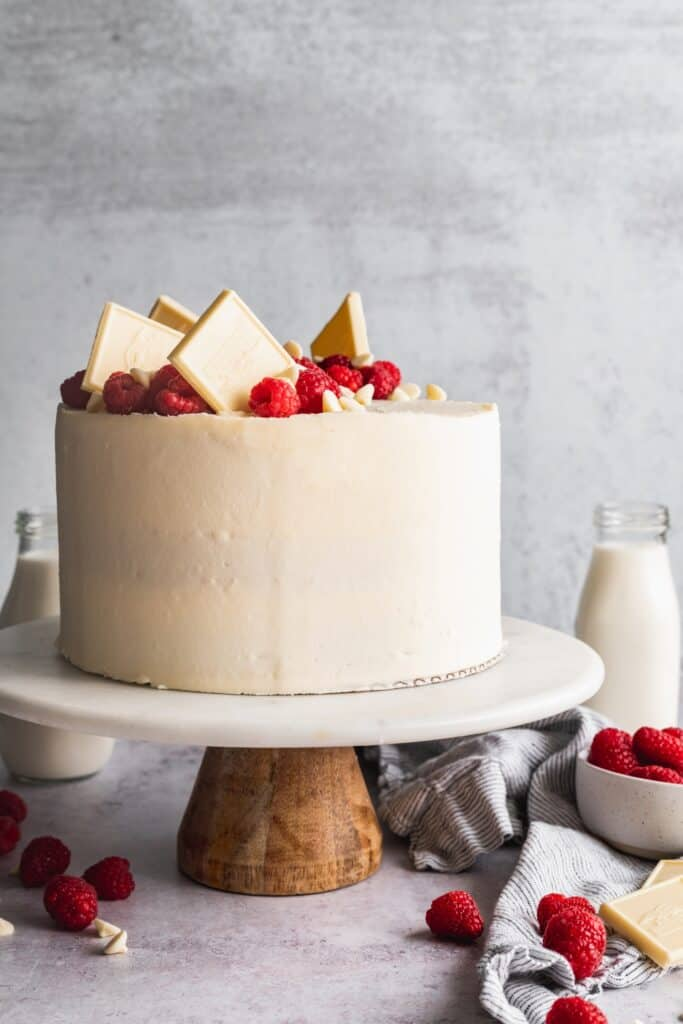 Raspberry white chocolate cake on a cake stand.