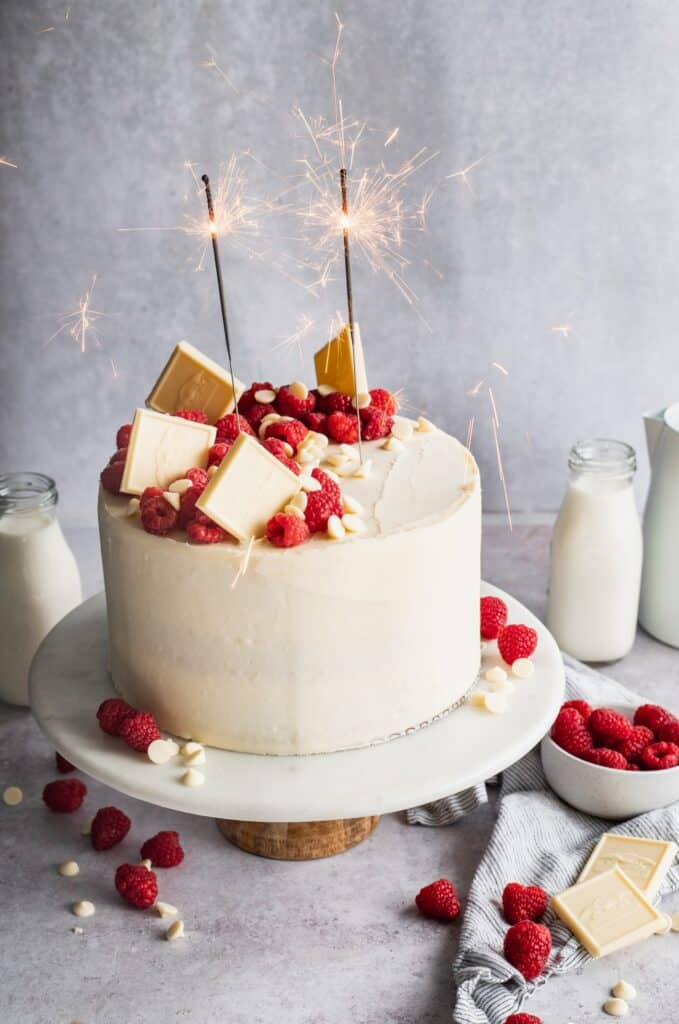Raspberry white chocolate cake on a cake stand with sparklers.