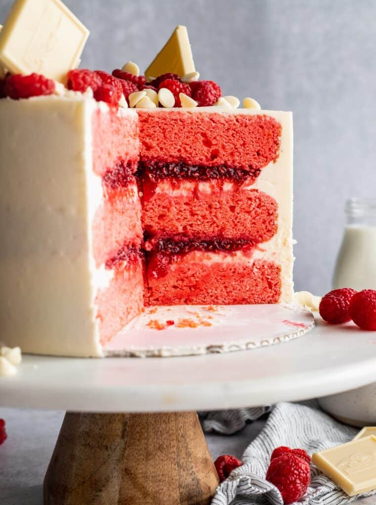 Cut into raspberry cake on a cake stand.