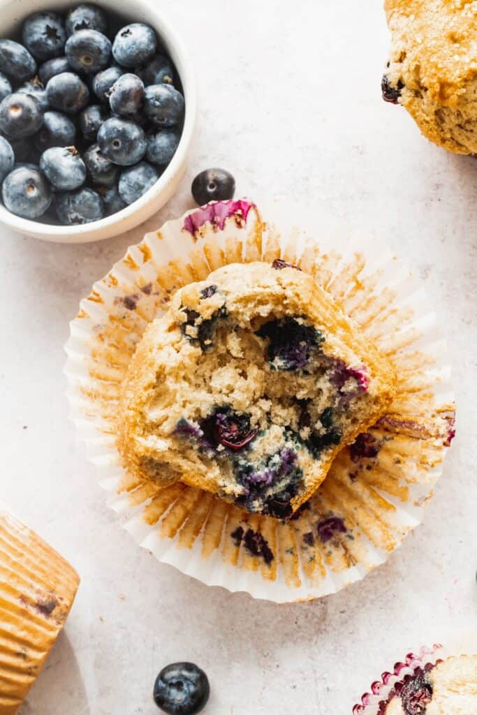 Sour cream blueberry muffin on its side with a bowl of blueberries.