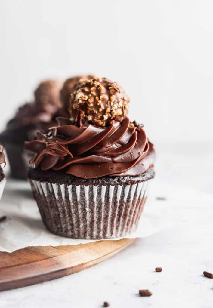 Chocolate fudge cupcakes on a board with a truffle on top