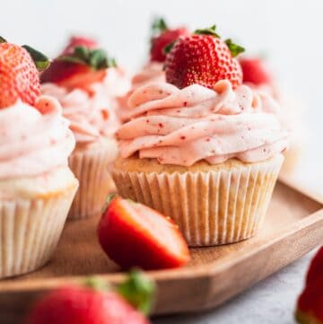 Strawberry filled cupcakes on a wooden platter.