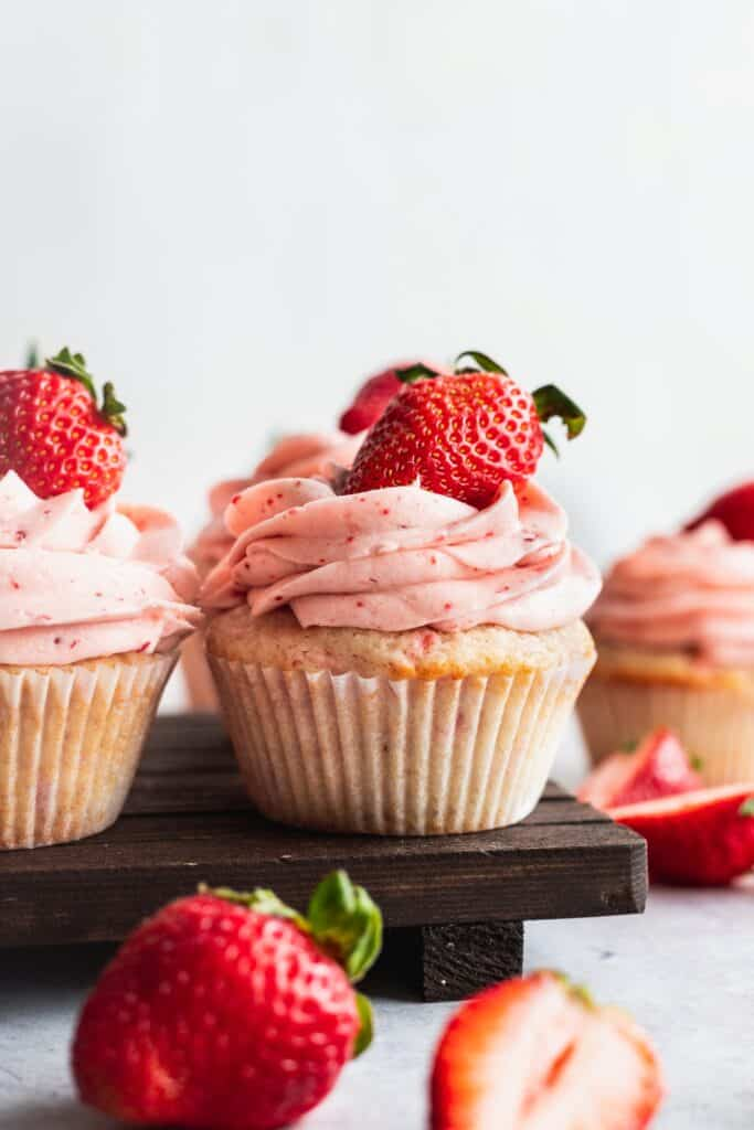 Strawberry filled cupcakes with extra strawberries on top.