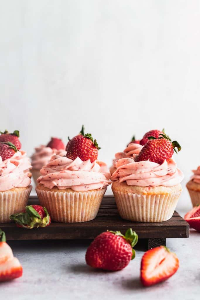A row of cupcakes on a wooden board.