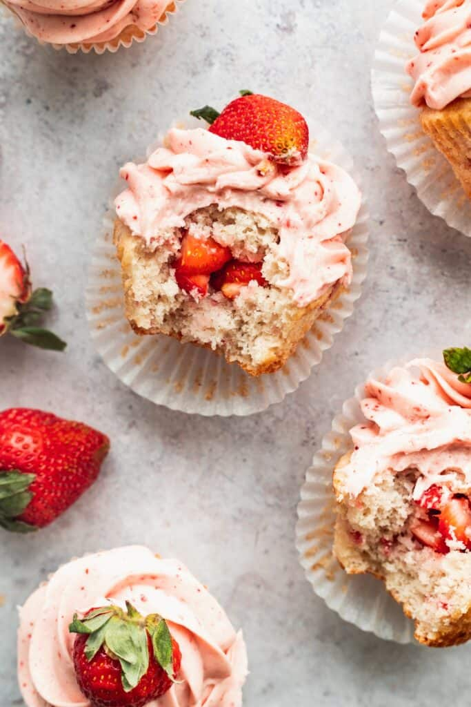 A bite missing from a strawberry filled cupcakes.