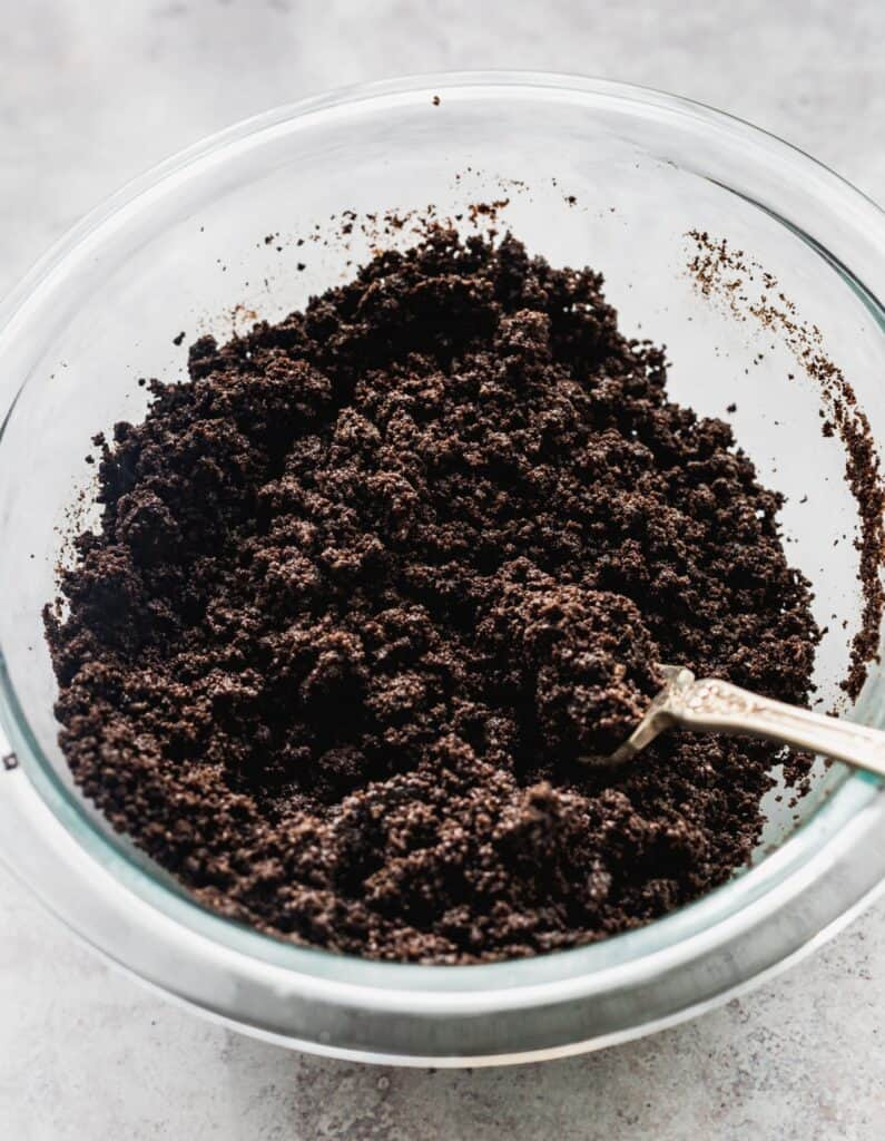 Oreo crumbs in a glass bowl.