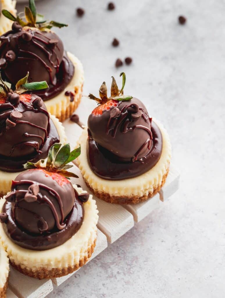 Mini chocolate strawberry cheesecakes on a wood board.