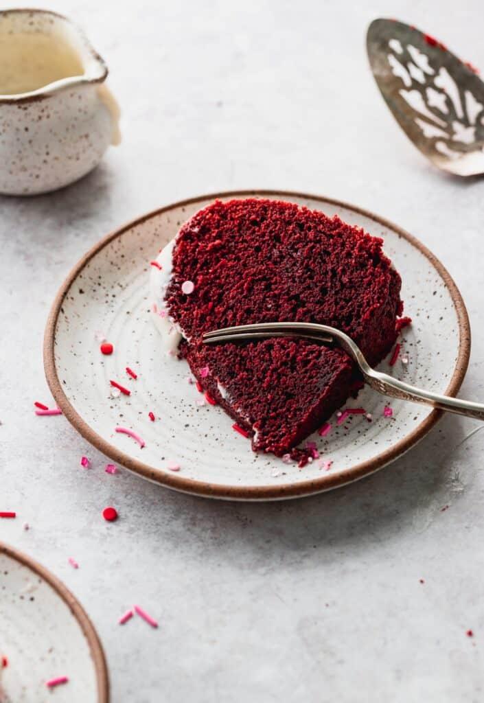 Red velvet bundt cake on plate with a fork inserted.