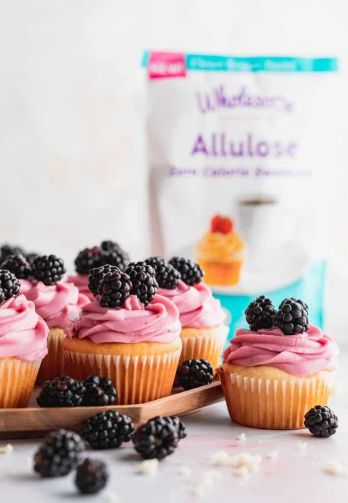 Blackberry cupcakes on a wooden plate.