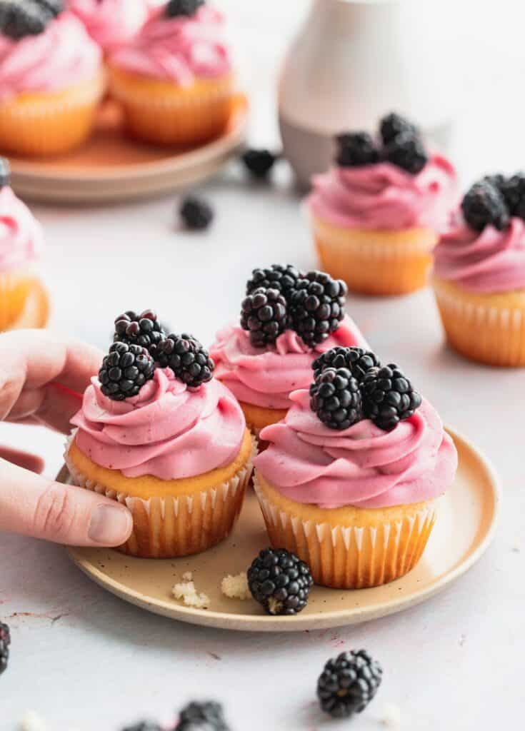 Blackberry cupcakes on a plate with a hand grabbing one.