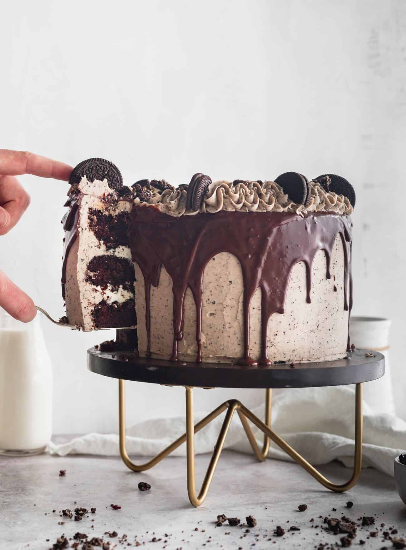 Cookies and cream cake with a slice being take out.