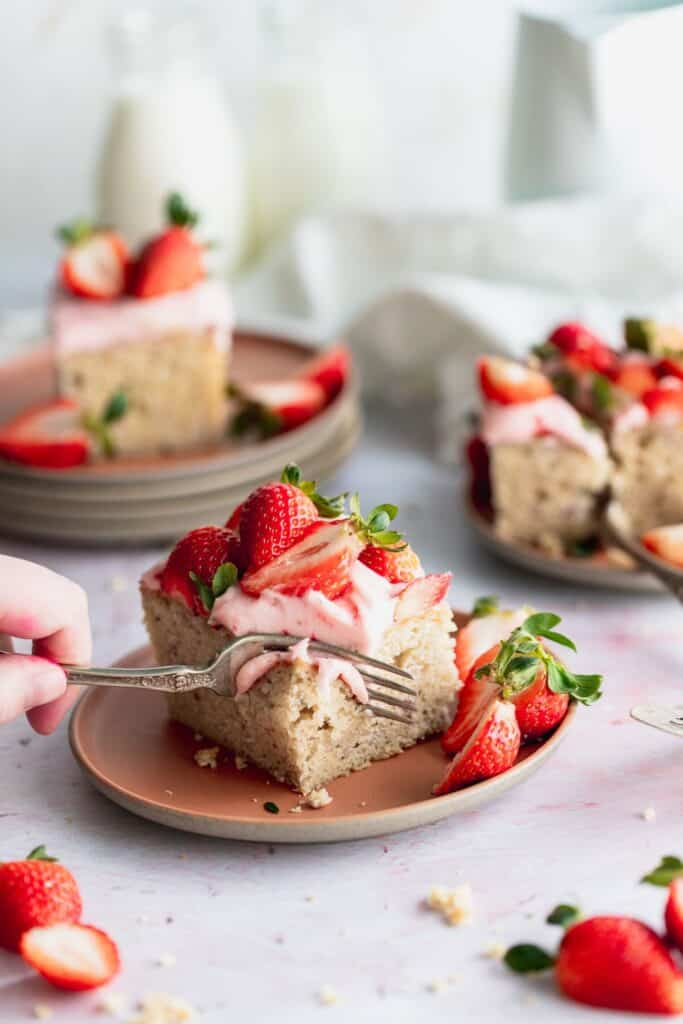 Cutting into a piece of strawberry sheet cake using a fork.