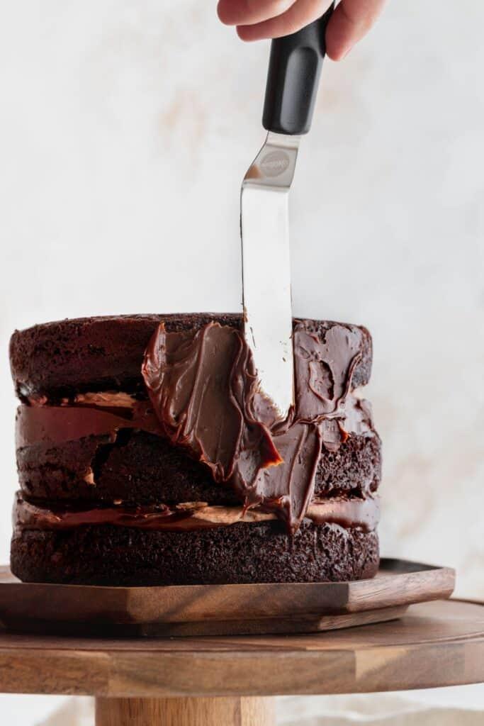 Spreading chocolate ganache on cake.