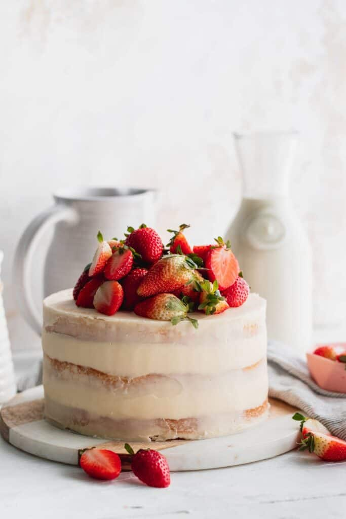 Strawberry semi-naked cake on a marble stand.