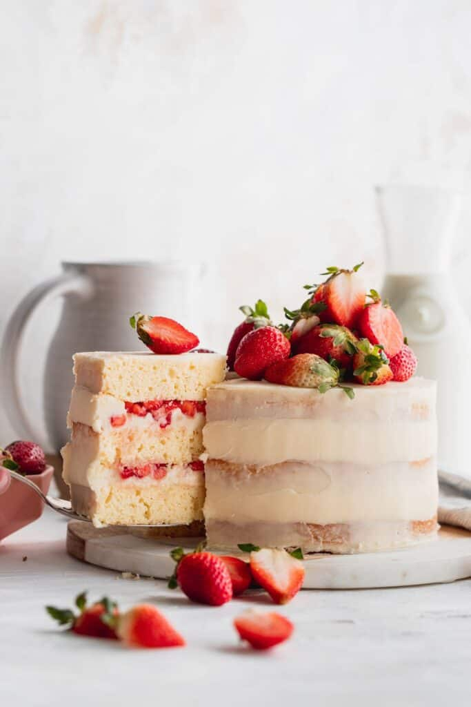 Taking a cake slice out of the strawberry semi-naked cake.