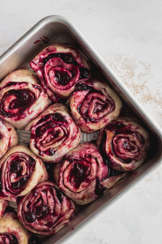 Raw cinnamon rolls rolled up in a pan.