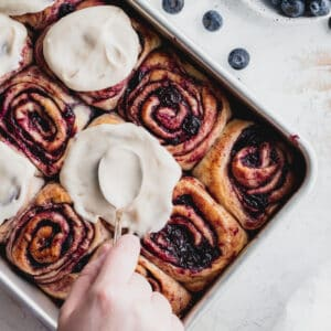 Spreading icing on top of blueberry cinnamon rolls.