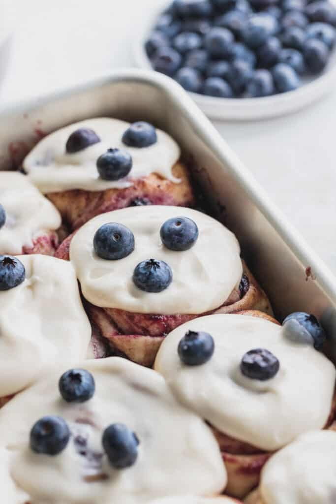 Blueberry cinnamon rolls in pan with fresh blueberries on top.